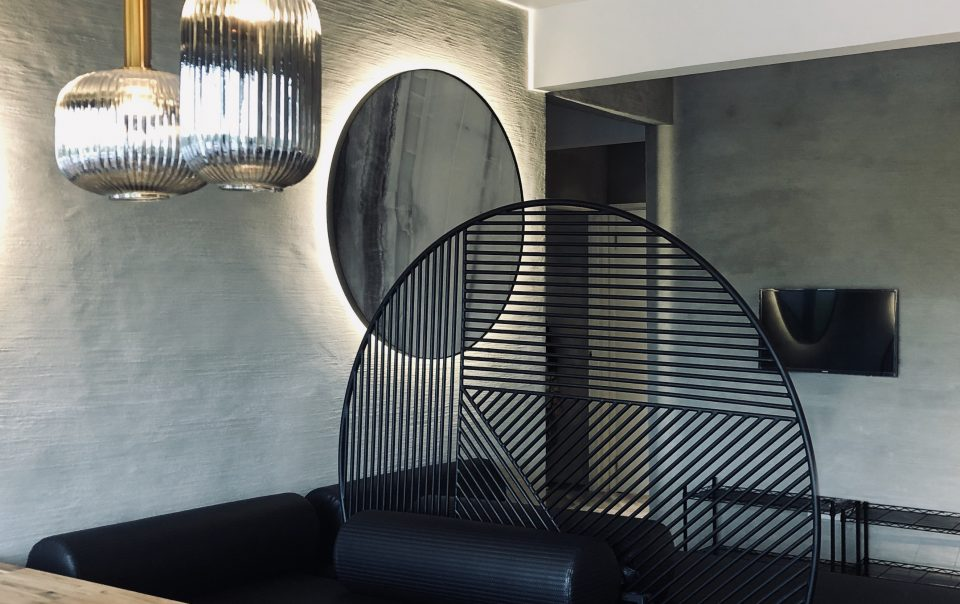 Design in Colonie with a glowing mirror,hanging lamps, and big black circular interior decoration