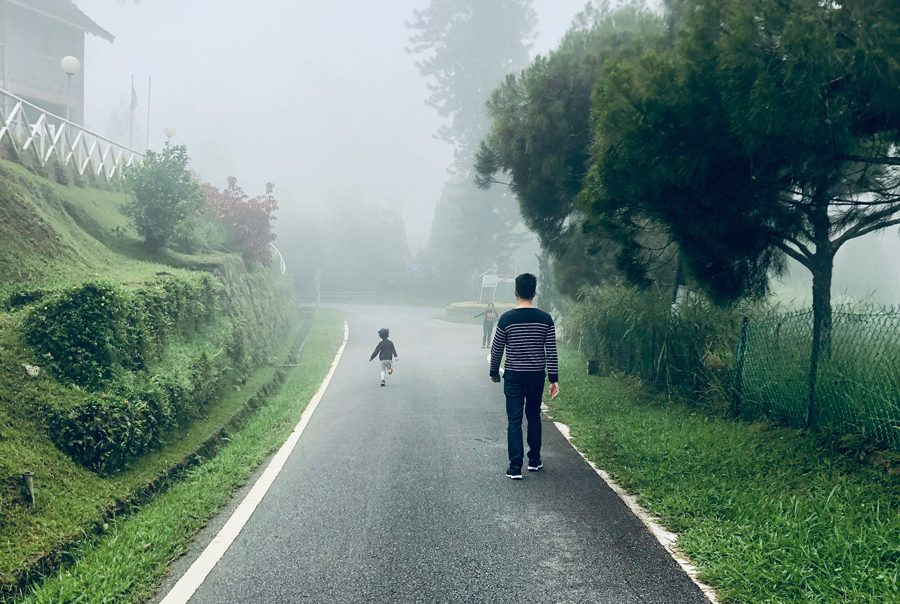 Father and child walking on paved road at Fraser's Hill,Pahang