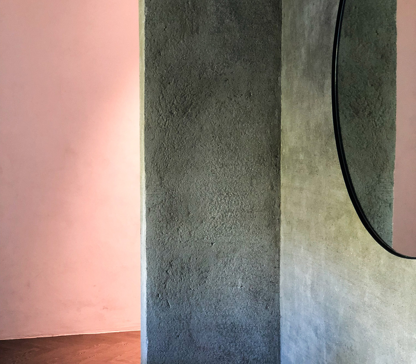 grey wall with circle mirror, pink background